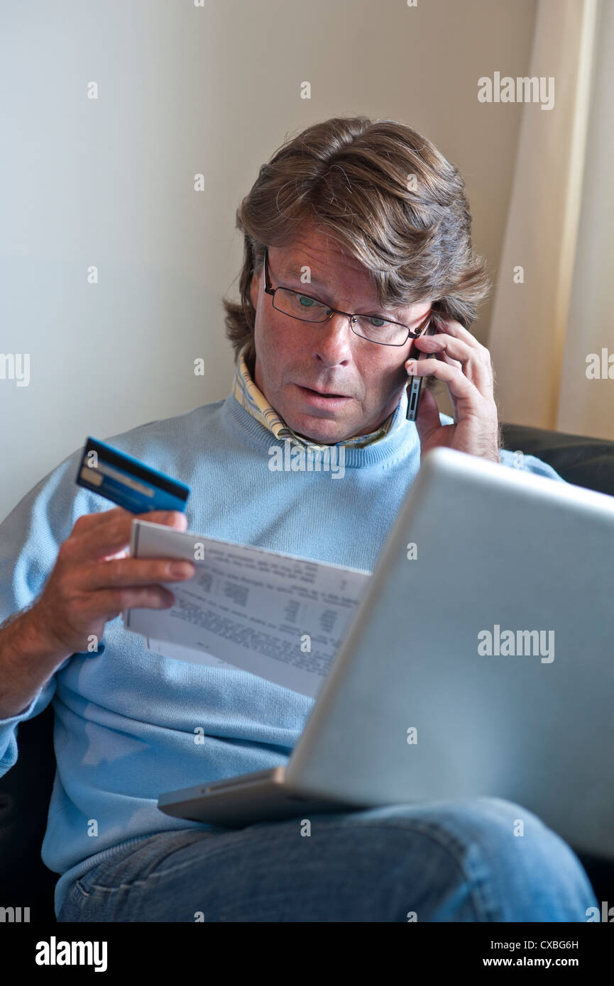 Worried mature man at home with a laptop computer on the telephone checking credit bank card financial transactions - Stock Image