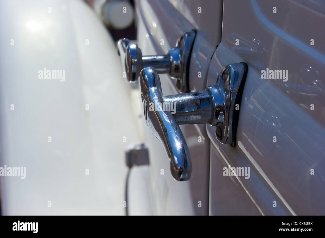 Close up of old chrome door handles on the side of an antique white automobile. - Stock Image