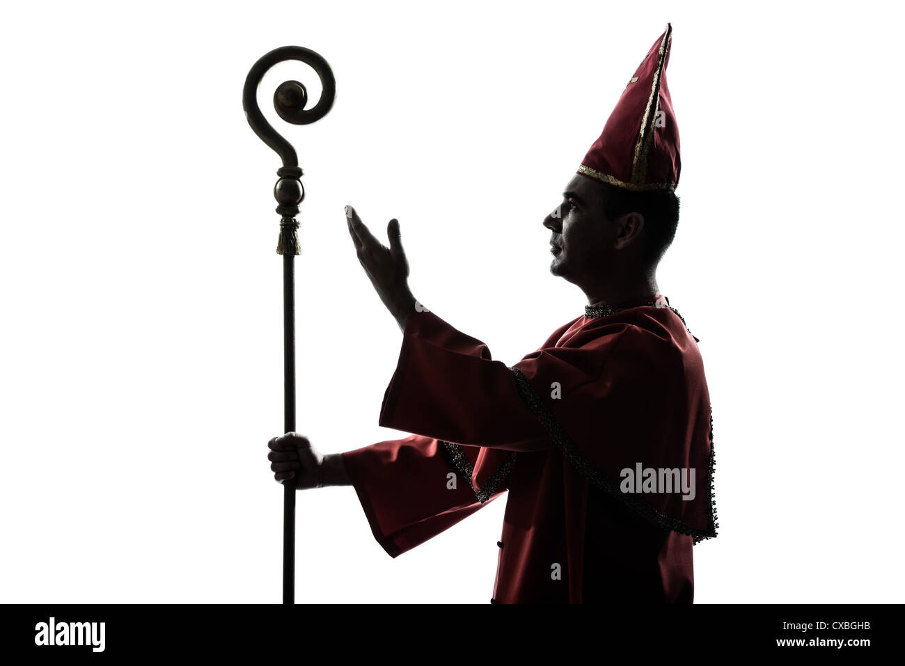 one man cardinal bishop silhouette saluting blessing in studio isolated on white background - Stock Image