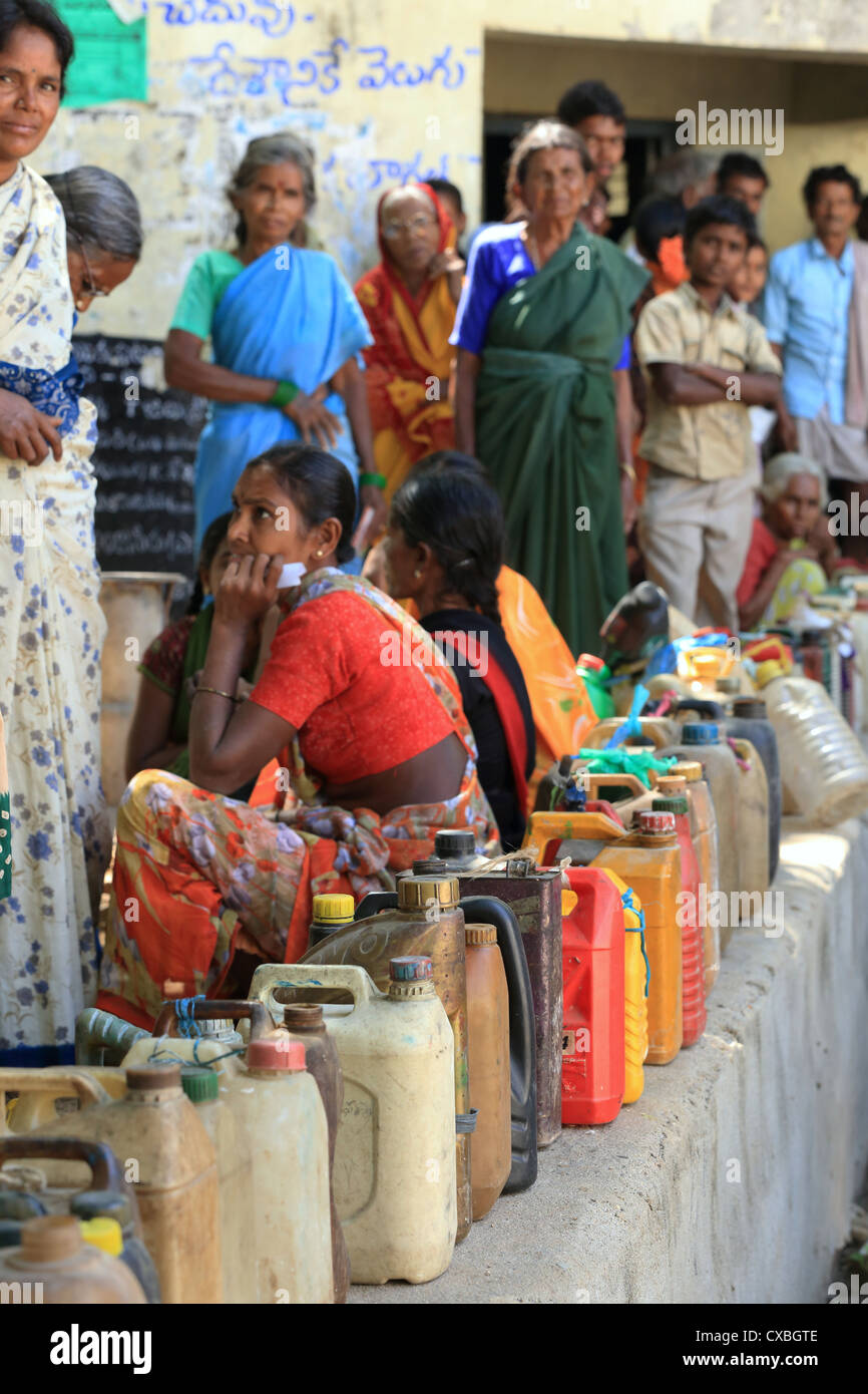 Indian rural people with queued containers to receive discounted kerosene Andhra Pradesh South India - Stock Image