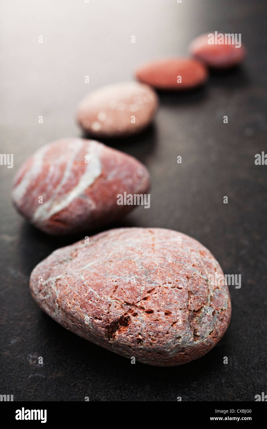 Curving line of red and grey pebbles arranged on dark textured background. - Stock Image