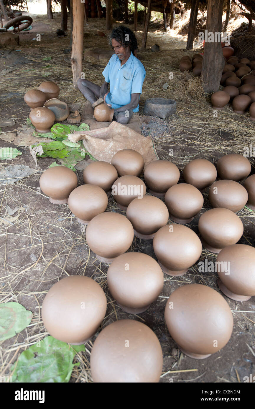 Potter making clay water pots in a thatched shelter in a rural village, near Rayagada, Orissa, India, Asia - Stock Image