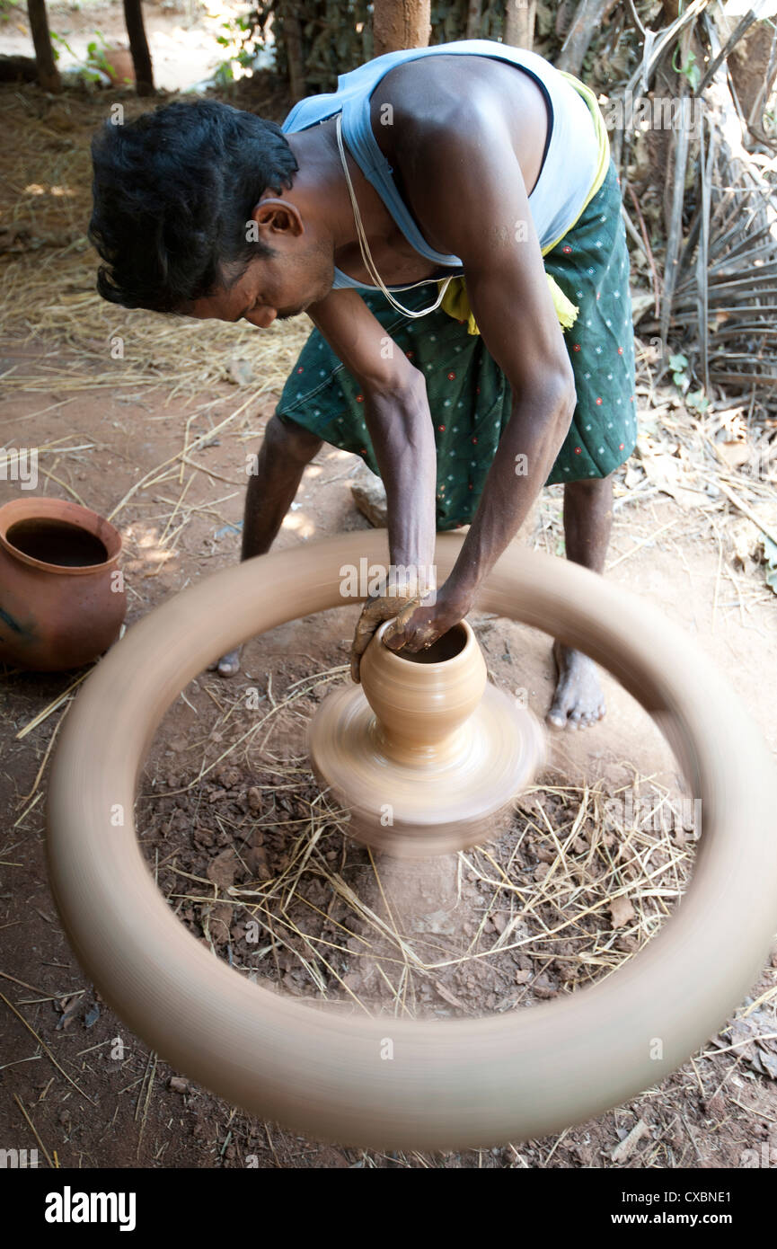 Village potter forming hand made clay pot on potter's wheel spinning in his village workshop, near Rayagada, - Stock Image