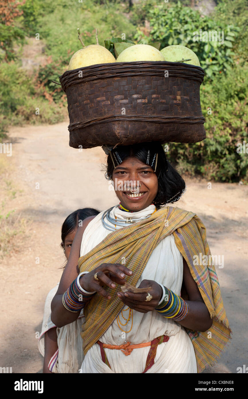 Dunguria Kondh tribeswoman wearing traditional tribal hairgrips and jewellery, carrying basket of melons, Bissam - Stock Image