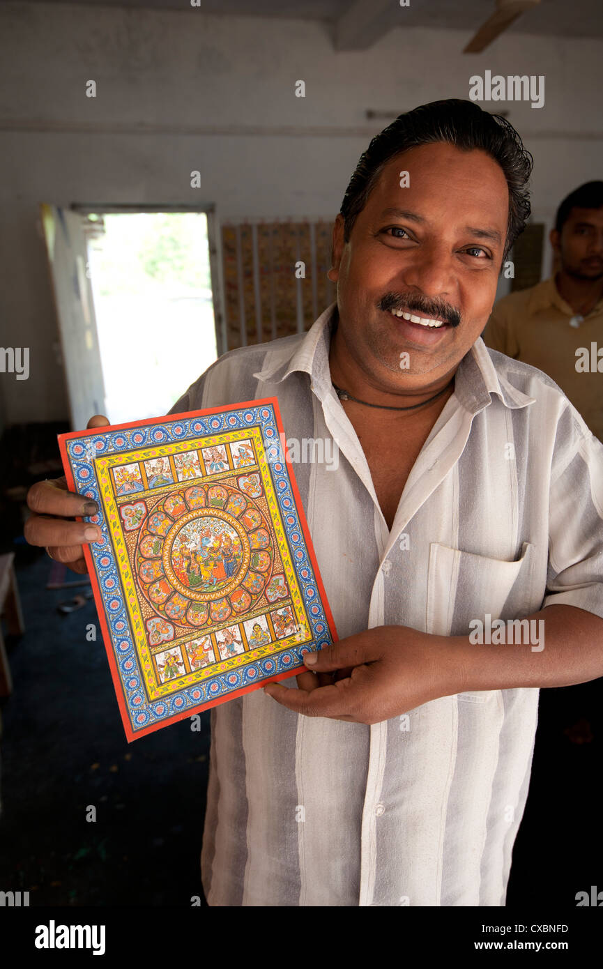 Raghurajpur artist holding up his detailed Orissa style painting depicting Hindu gods and patterns, Raghurajpur, - Stock Image