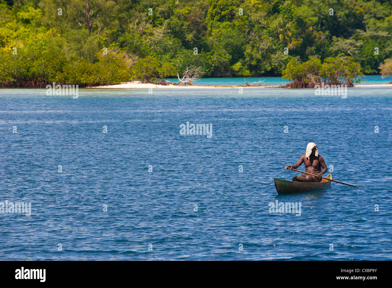 Man sitting in his canoe, Marovo Lagoon, Solomon Islands, Pacific - Stock Image