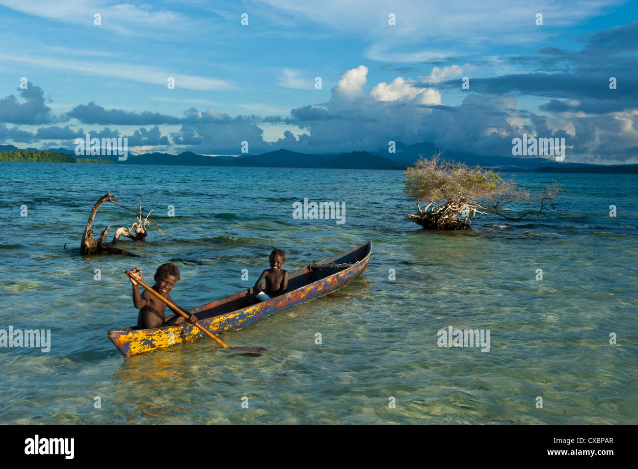 Young boys fishing in the Marovo Lagoon below dramatic clouds, Solomon Islands, Pacific - Stock Image