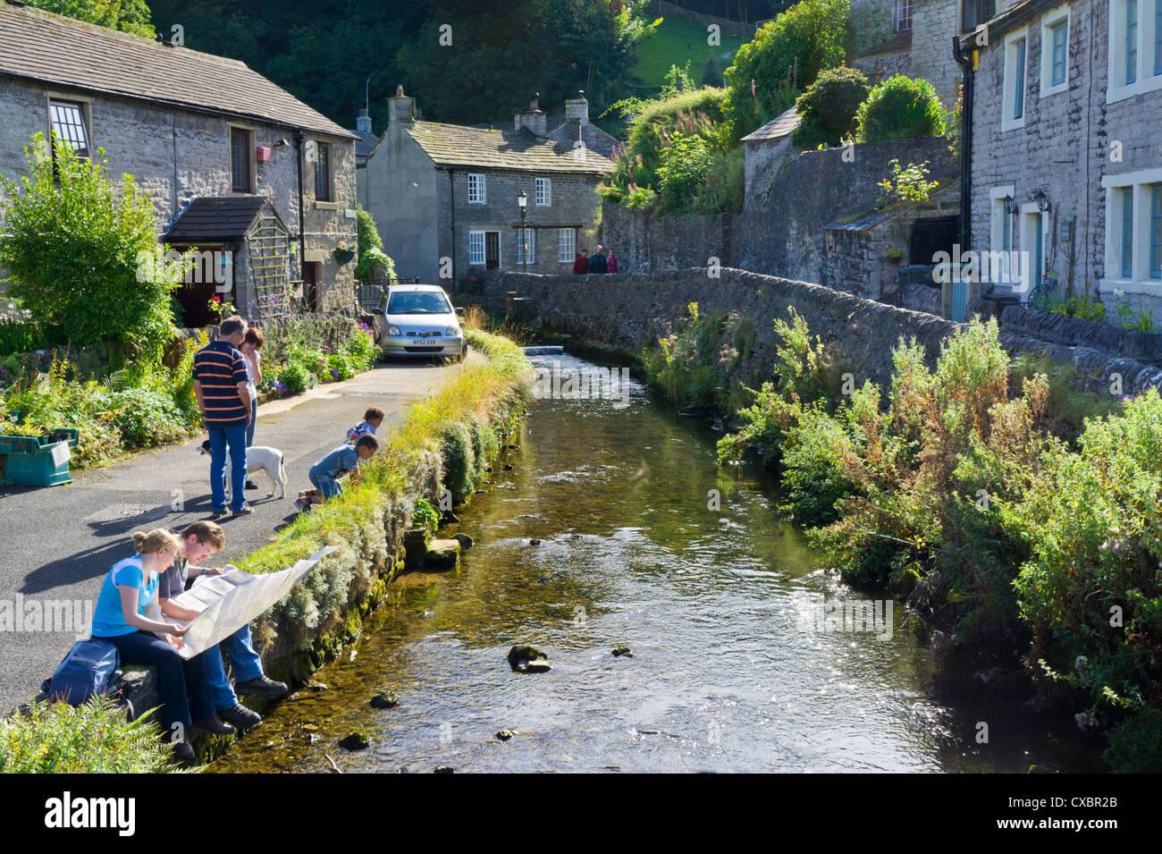 Castleton village centre and Peakshole water flowing past cottages Derbyshire Peak District National Park England - Stock Image
