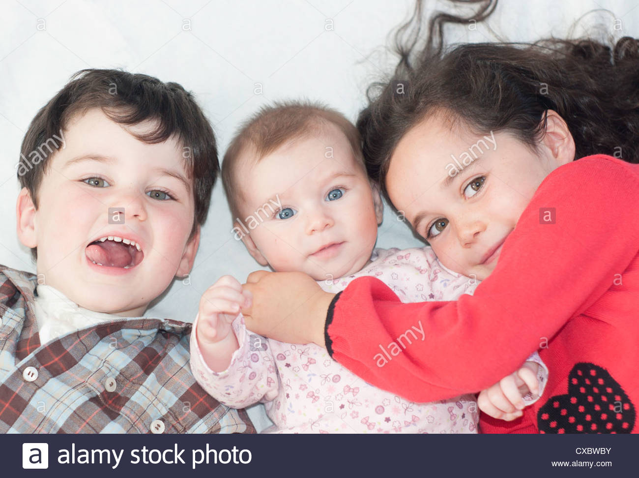 A boy and two girls, three siblings - Stock Image