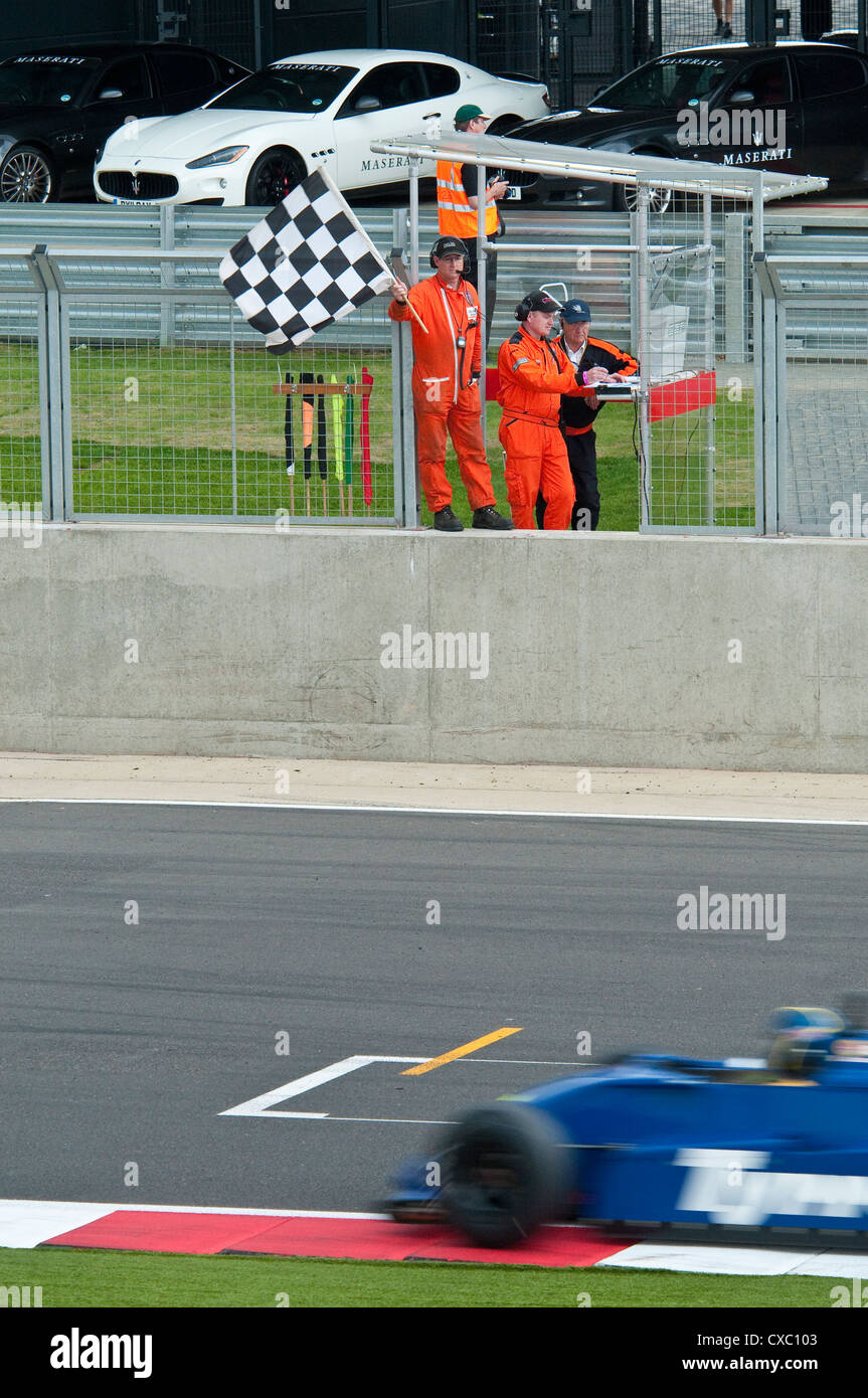 Chequered Flag Being Waved at a Race Car - Stock Image