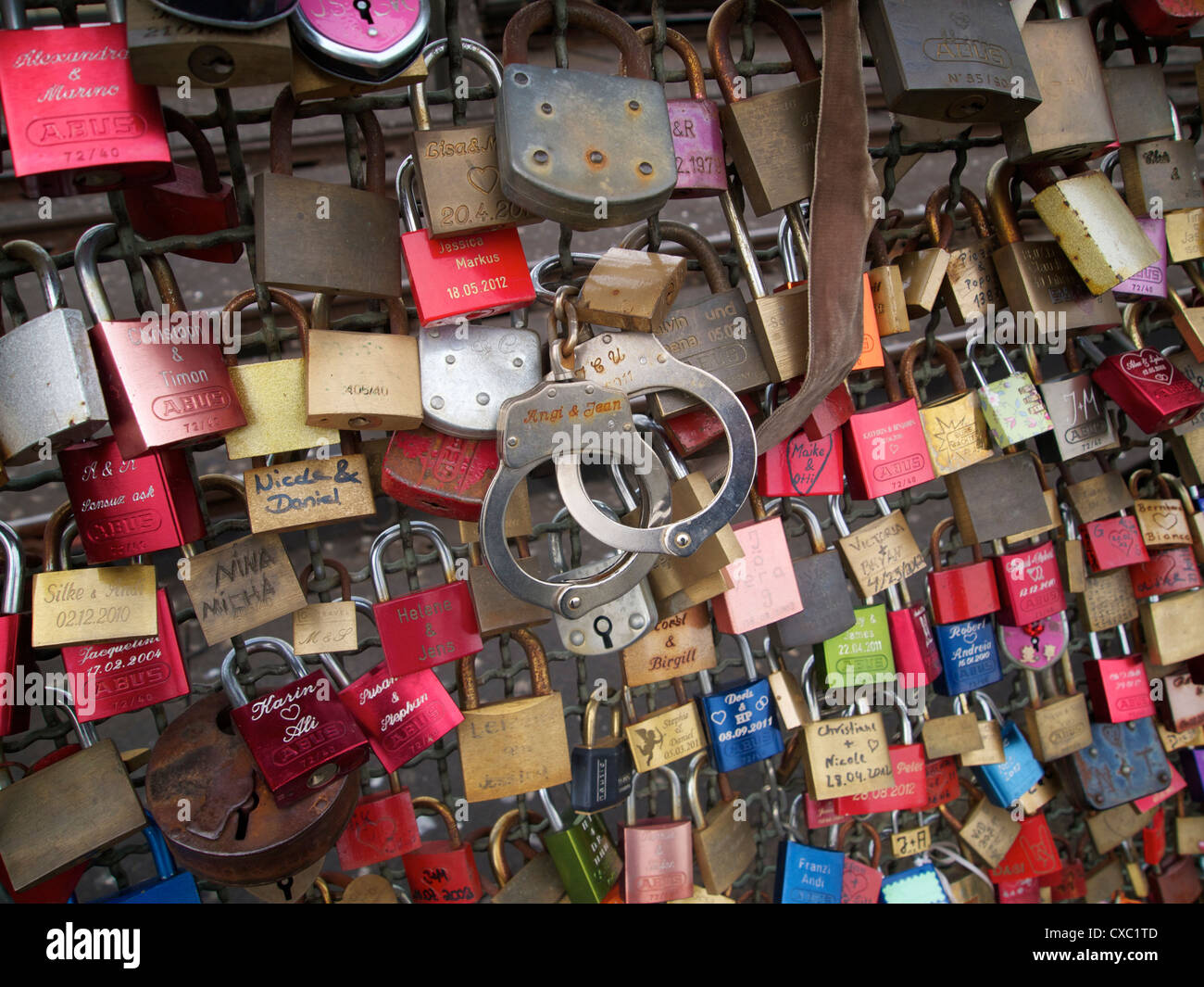 Padlocks and handcuffs symbolizing relationships on the Hohenzollernbrucke railway bridge in Cologne, Germany - Stock Image