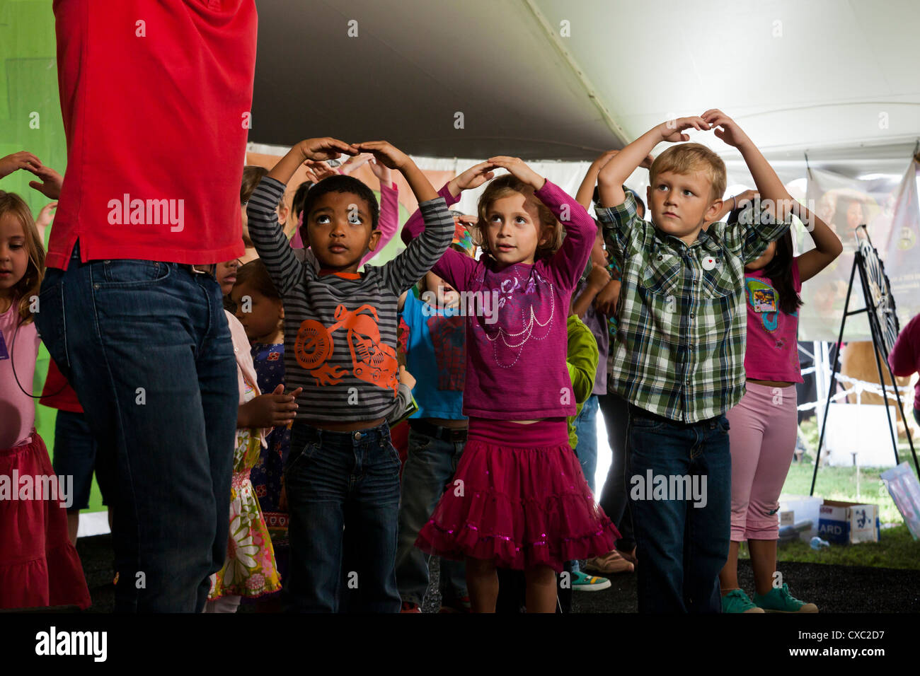 Children dancing on stage with an adult - USA - Stock Image