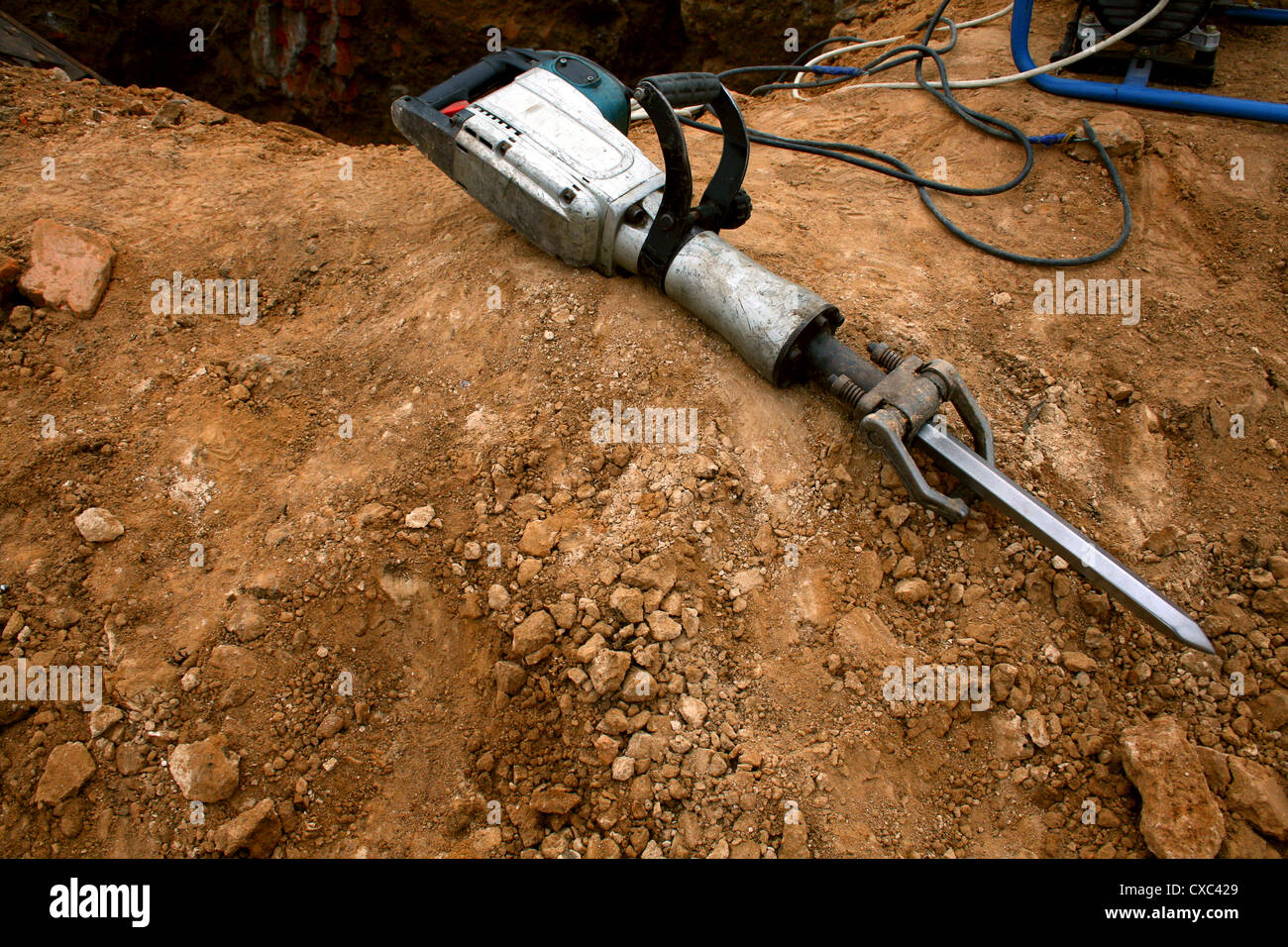 Grungy pneumatic hammer lying on the ground - Stock Image