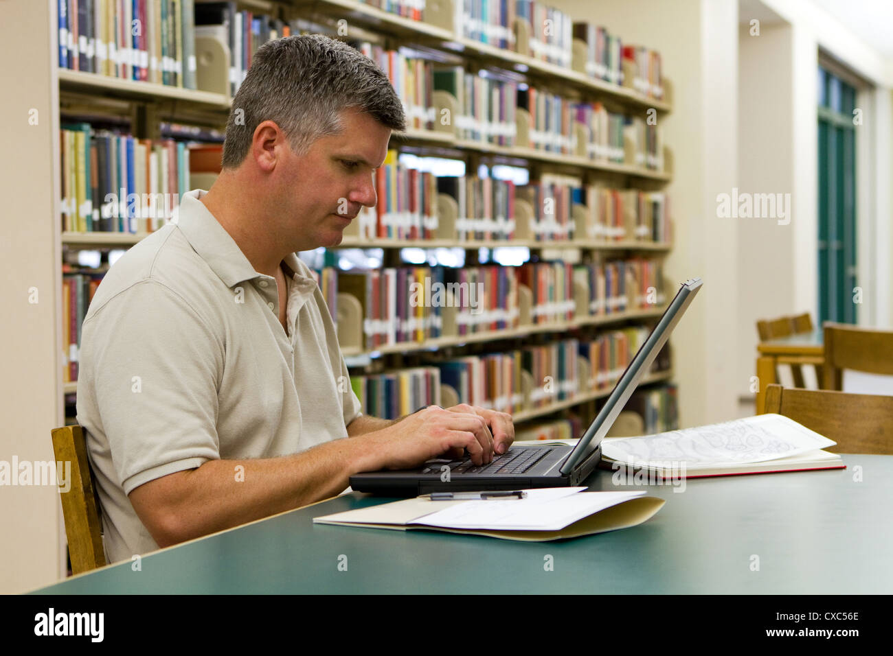 Middle-aged college student types on a laptop in the library. - Stock Image