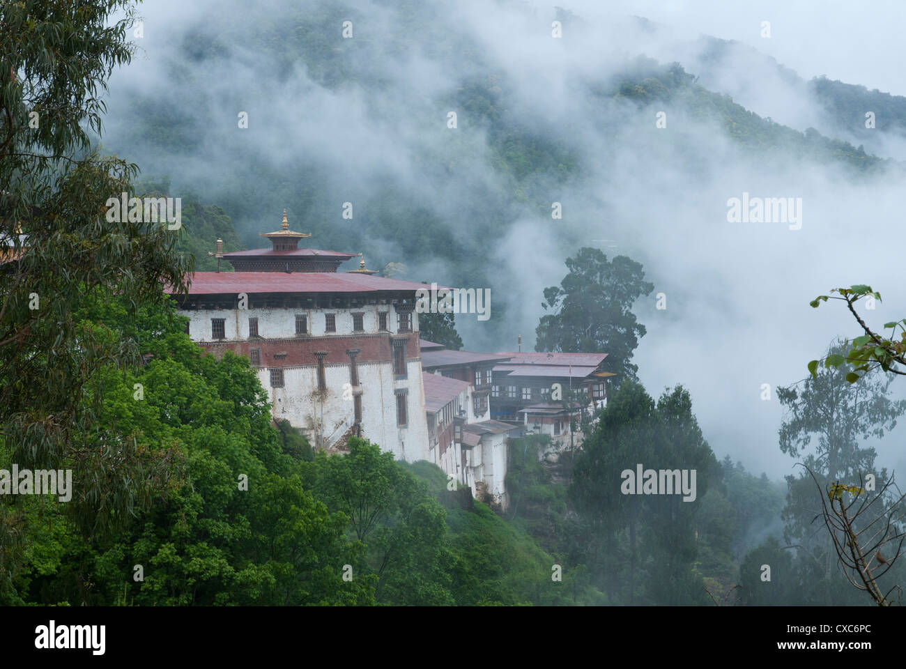 View of the Dzong with hills and fog, Trongsa, Bhutan, Asia - Stock Image