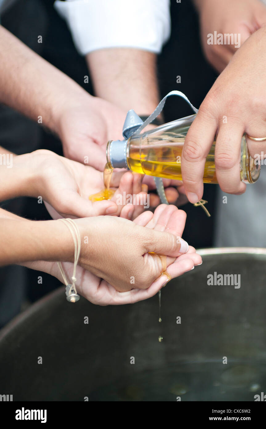 Orthodox baptism ritual . The priest pours olive oil in the hands of the Godparents above the baptismal font and - Stock Image