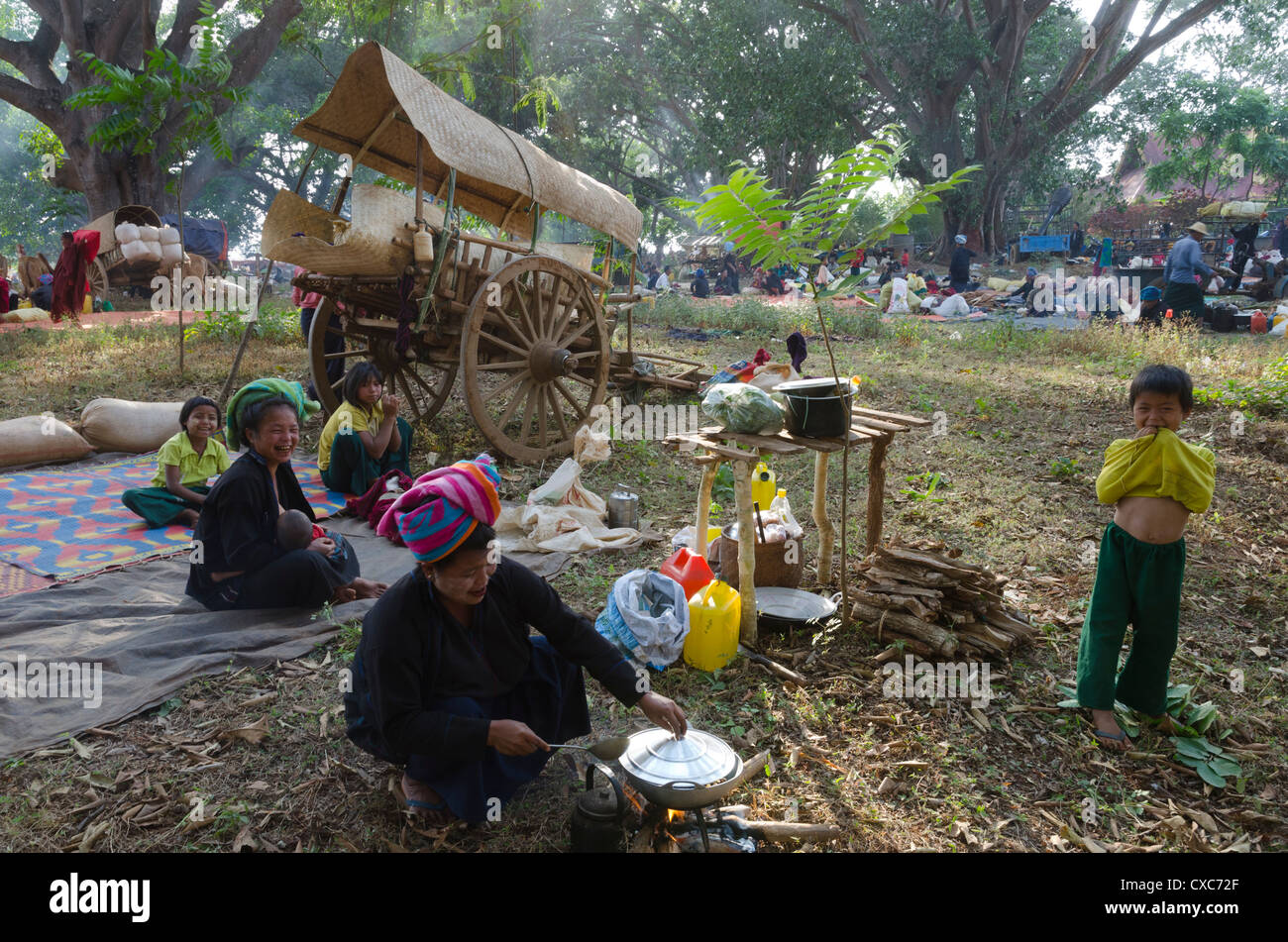 Pa Oh minority women and children cooking next to their bull cart, Kakku festival, Shan State, Myanmar (Burma), - Stock Image