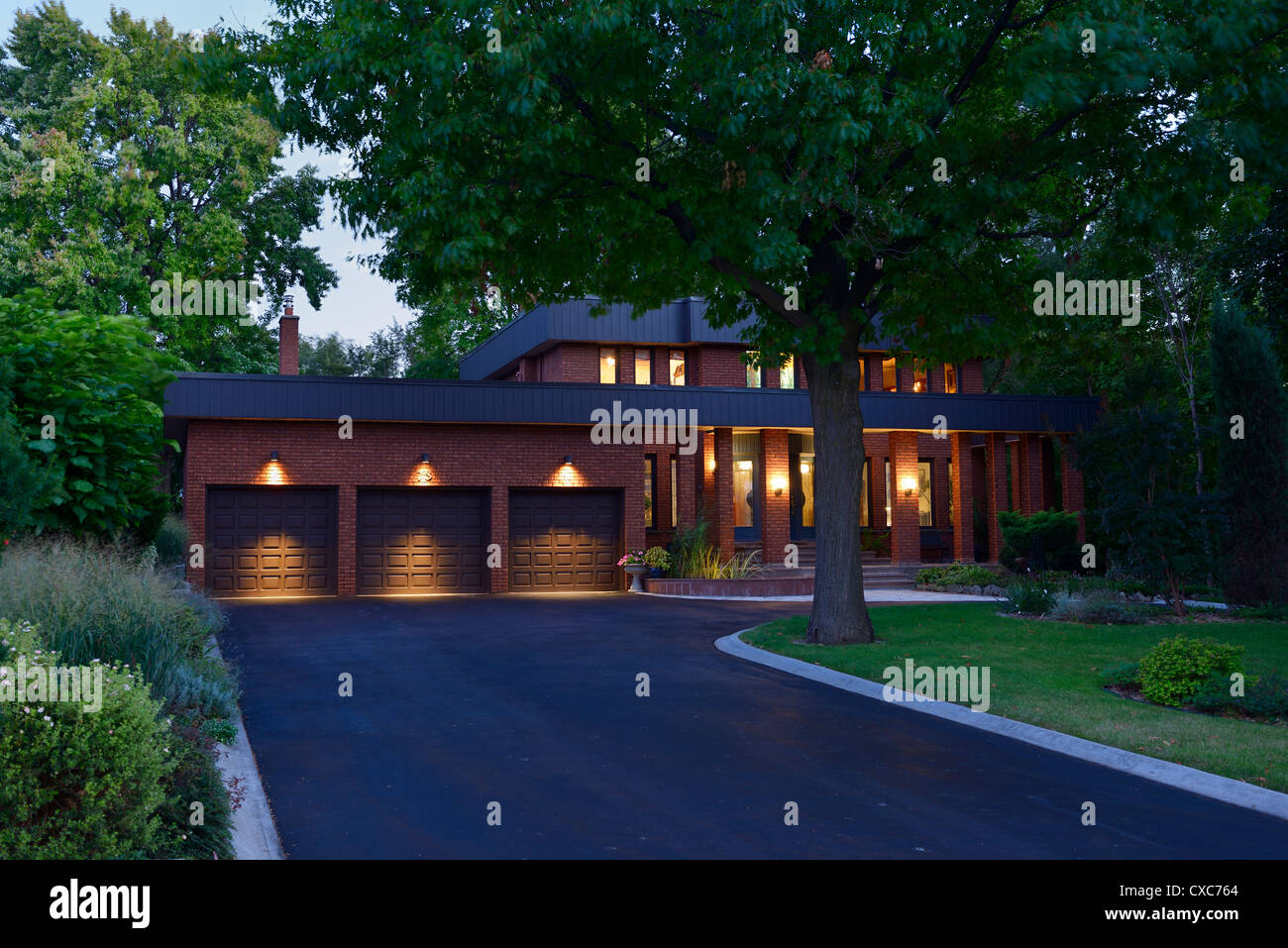 Red brick house with lights on and circular paved driveway and triple garage at dusk - Stock Image