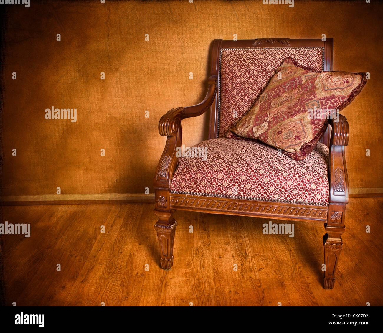 Vintage style armchair against textured wall - Stock Image