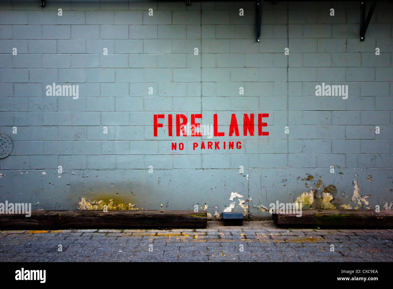 Grungy brick wall with bright red words indicating Fire Lane No Parking.  Good for backdrop - Stock Image