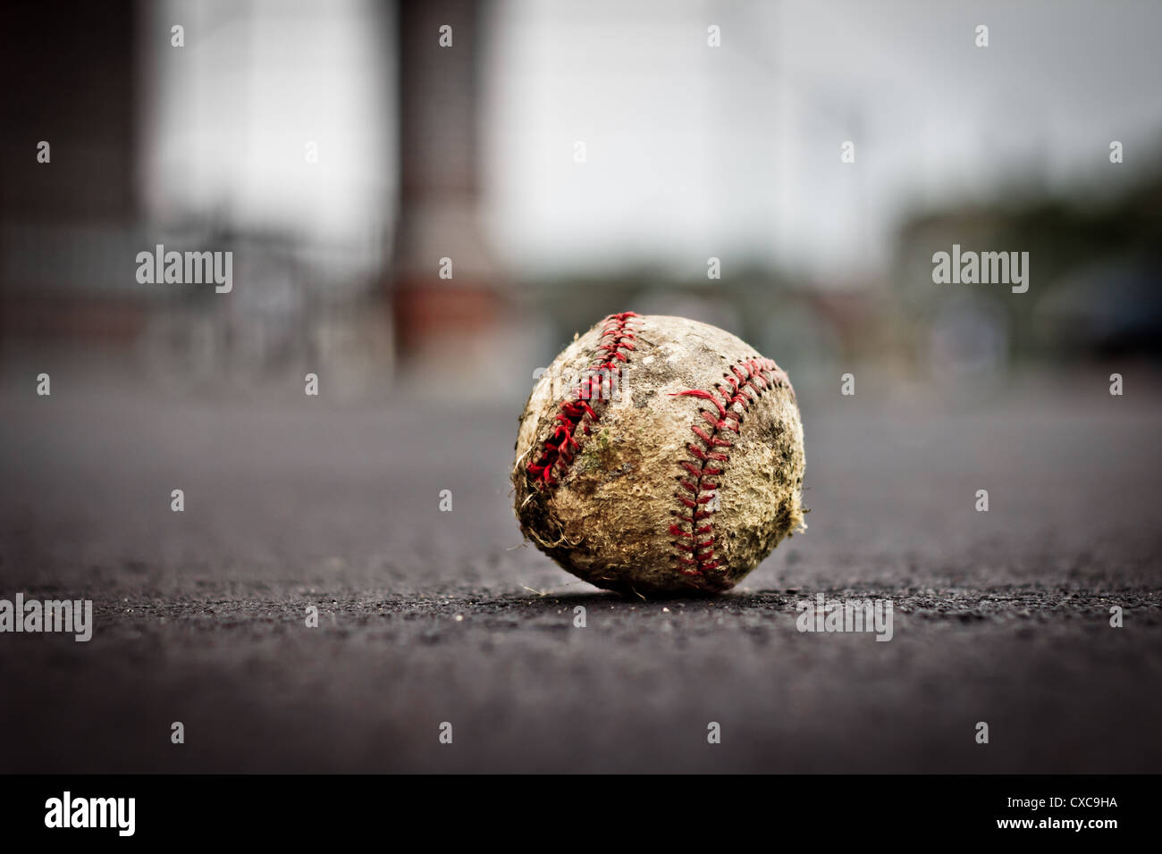Grungy well worn old baseball on ground with very shallow depth of field - Stock Image