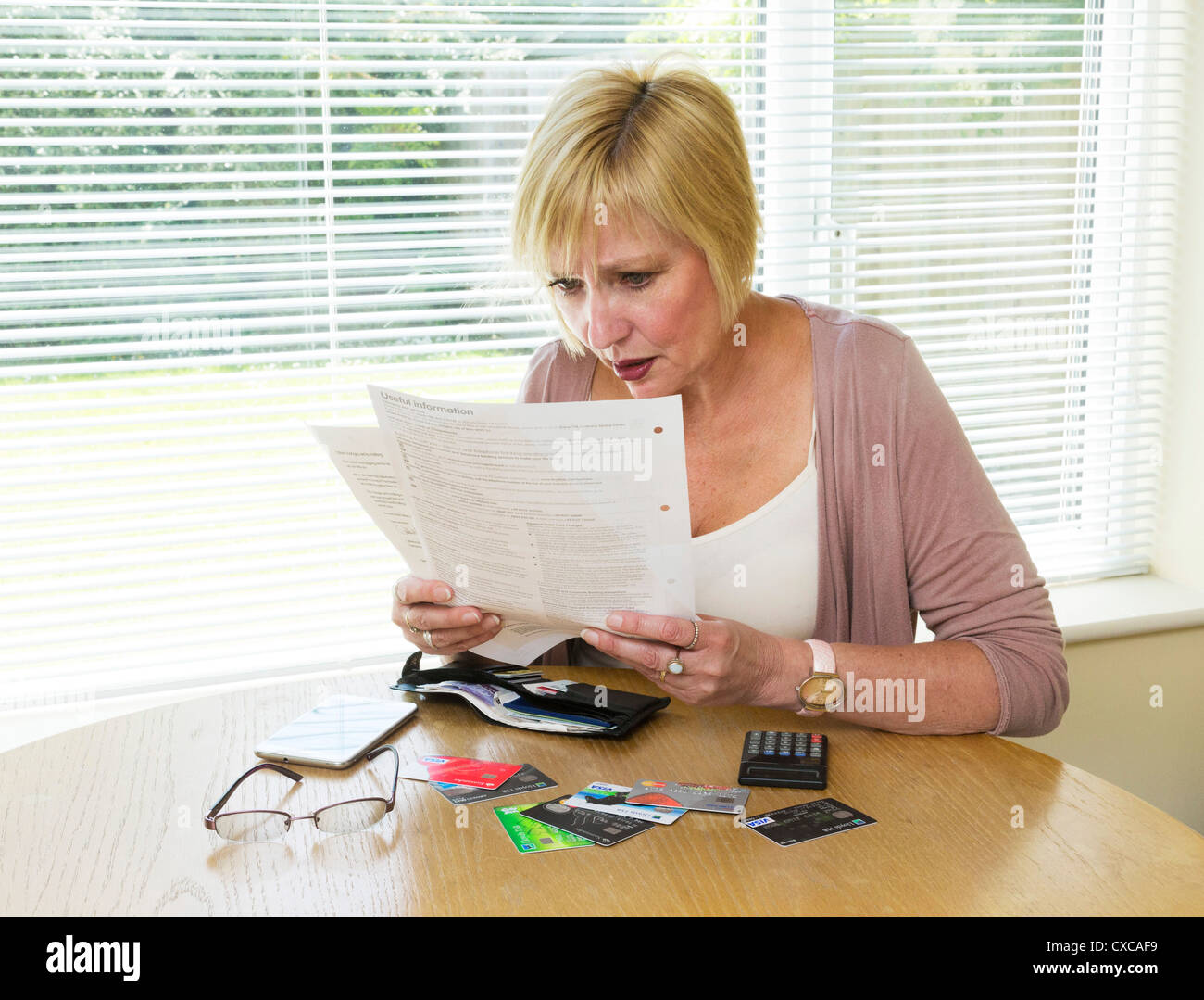 woman shocked at reading her credit card bill - Stock Image