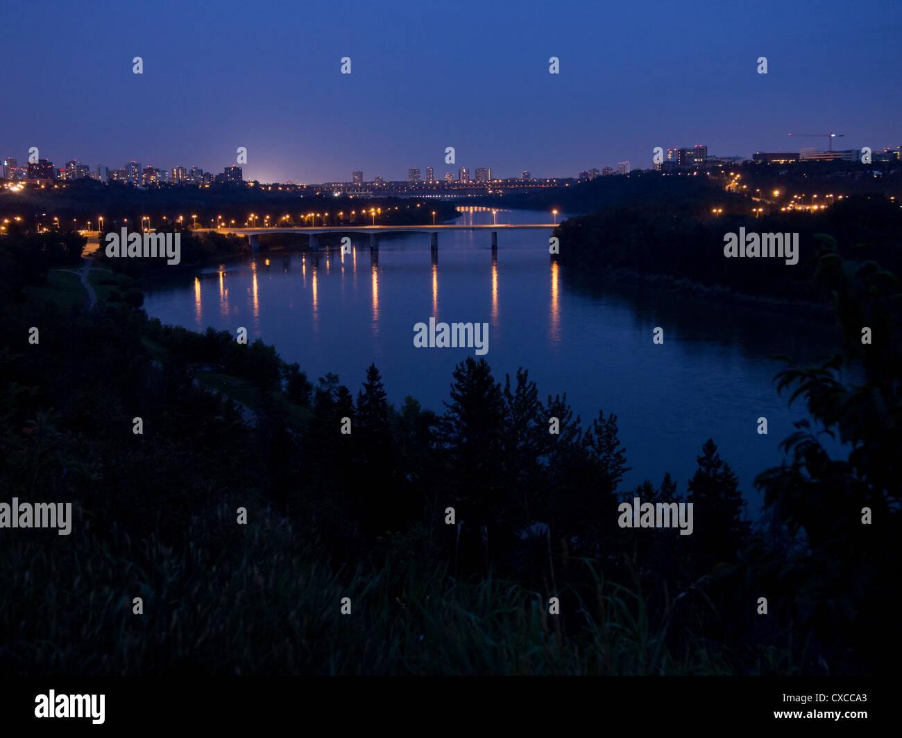 Edmonton Skyline at night featuring the bridges across the Saskatchewan  River. Lights glow in this evening view - Stock Image