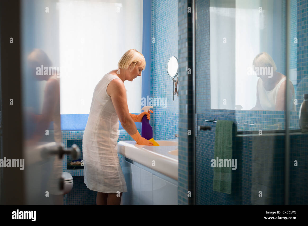 mature woman cleaning bathroom with spray detergent - Stock Image