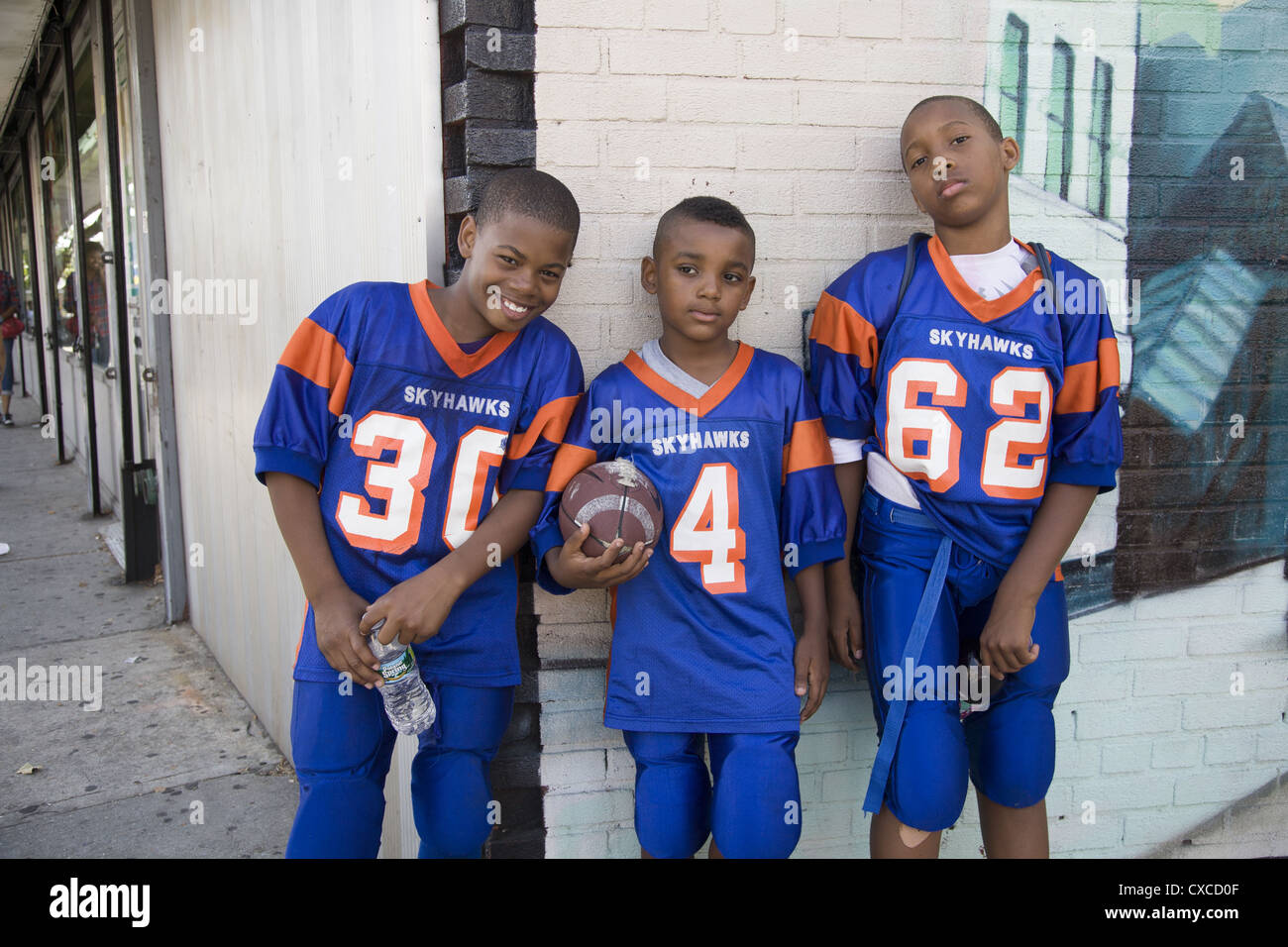 15117d3e0 Three young friends & teammates in uniform after their first football game  of the year.