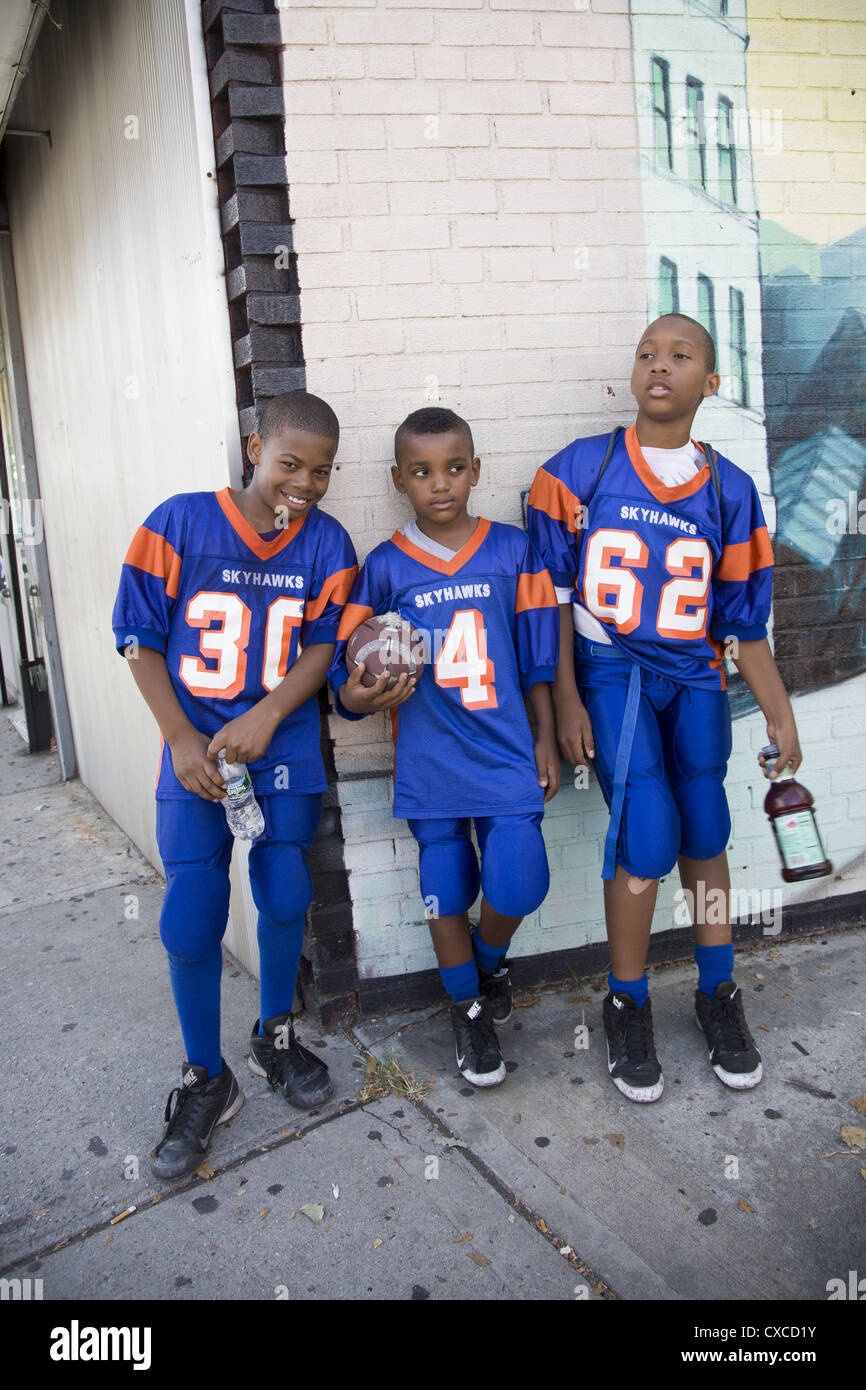 2acc15e84 Three young friends & teammates in uniform after their first football game  of the year. Brooklyn, NY.
