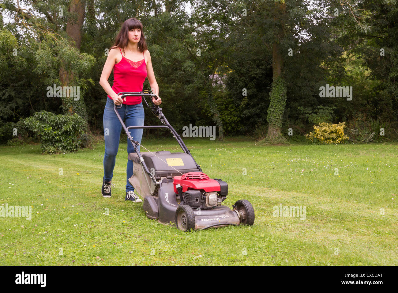 woman mowing lawn - Stock Image