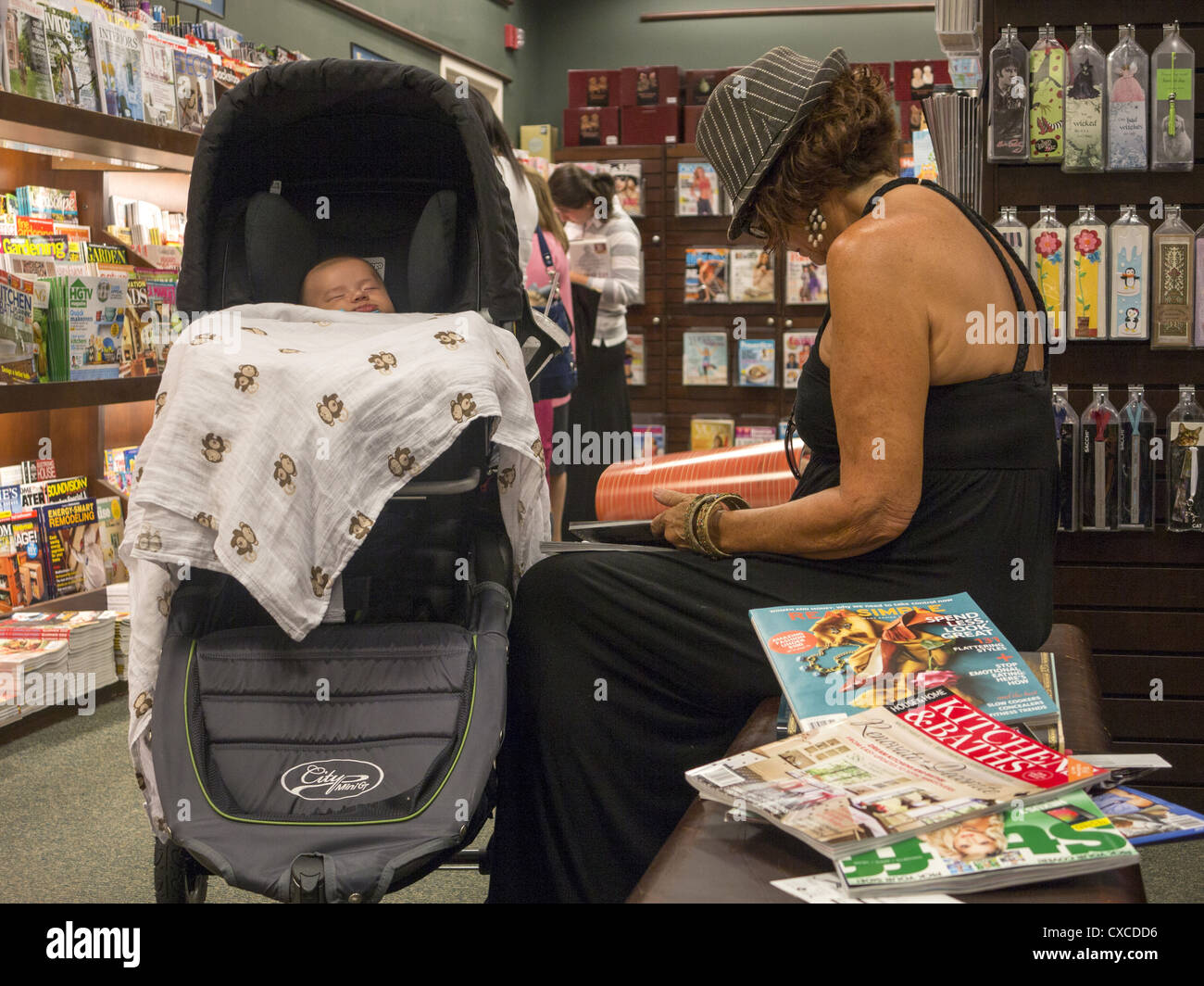 Grandma reads magazines while her grandchild snoozes at a Barnes & Noble bookstore in Park Slope, Brooklyn, - Stock Image