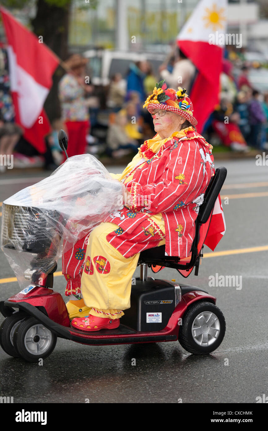 Female clown in motorized medical chair during 2012 Victoria Day Parade-Victoria, British Columbia, Canada. - Stock Image