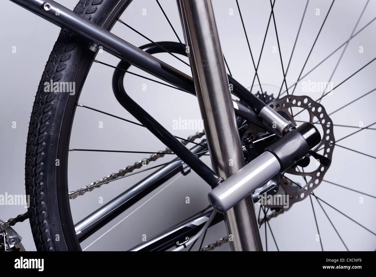 Bicycle attached to a metal pole with a U lock - Stock Image