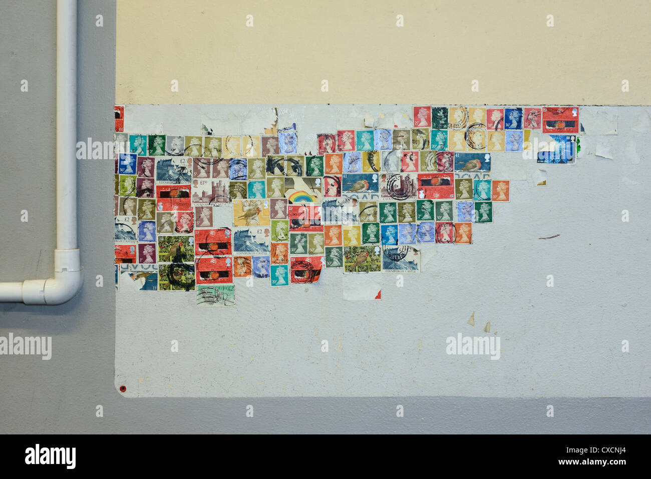 A collection of UK stamps stuck to a wall - Stock Image