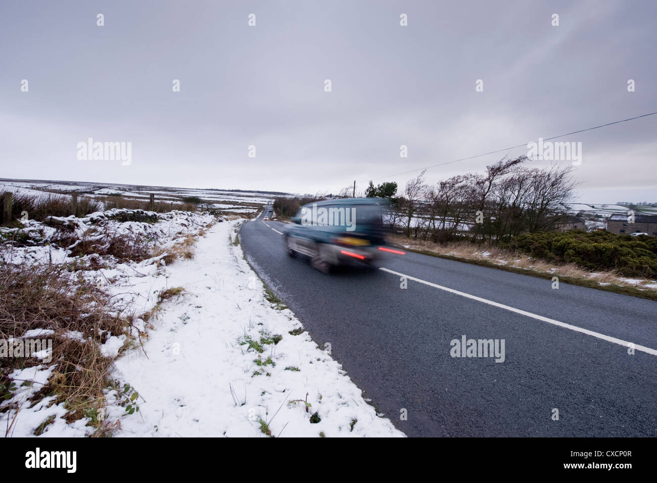 Blurred motion of Toyota Land Cruiser 4x4 traveling past white fields along moorland road on cold, snowy winter's - Stock Image
