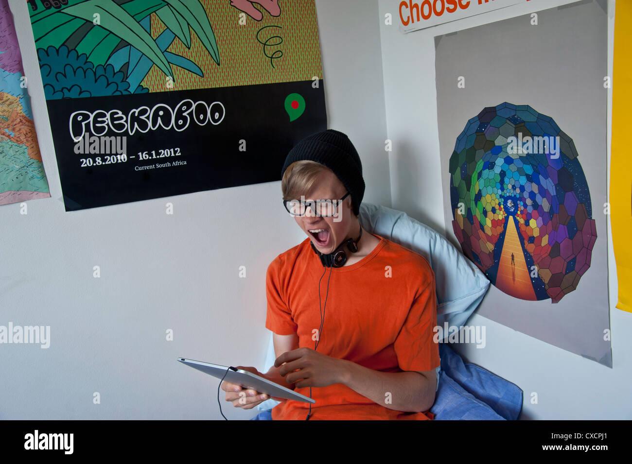 Yawning teenage boy with iPad tablet computer in his bedroom during his school exam studies - Stock Image