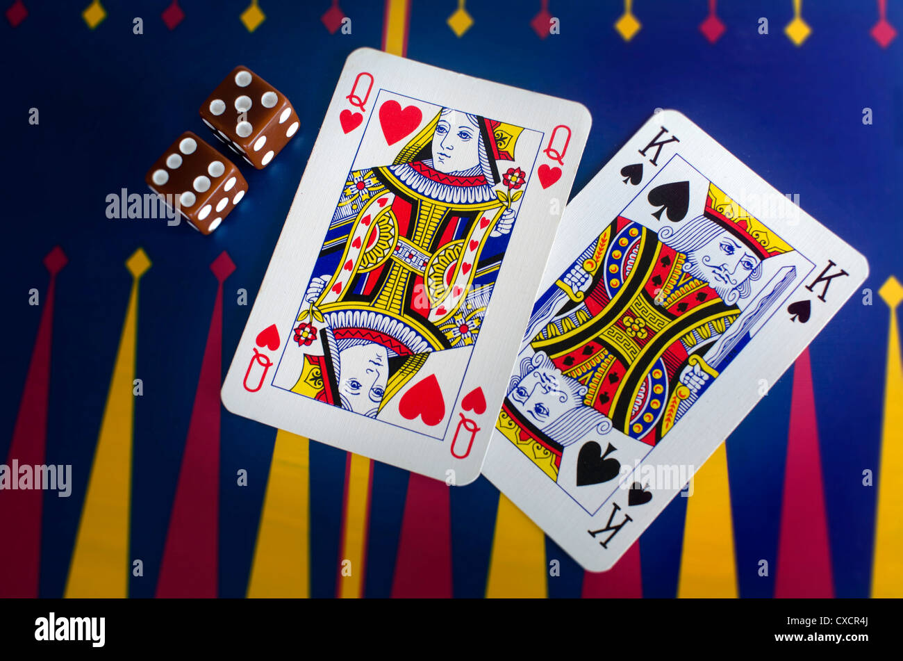 Queen and King playing cards with dice on a colorful casino table surface. Stock Photo