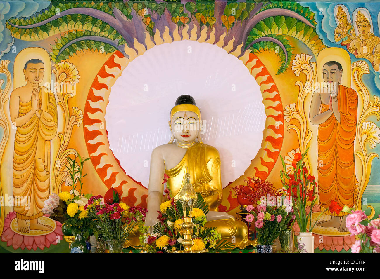 Enlightened Buddha Statue Sitting Under the Bodhi Tree with Painted Mural Background Stock Photo