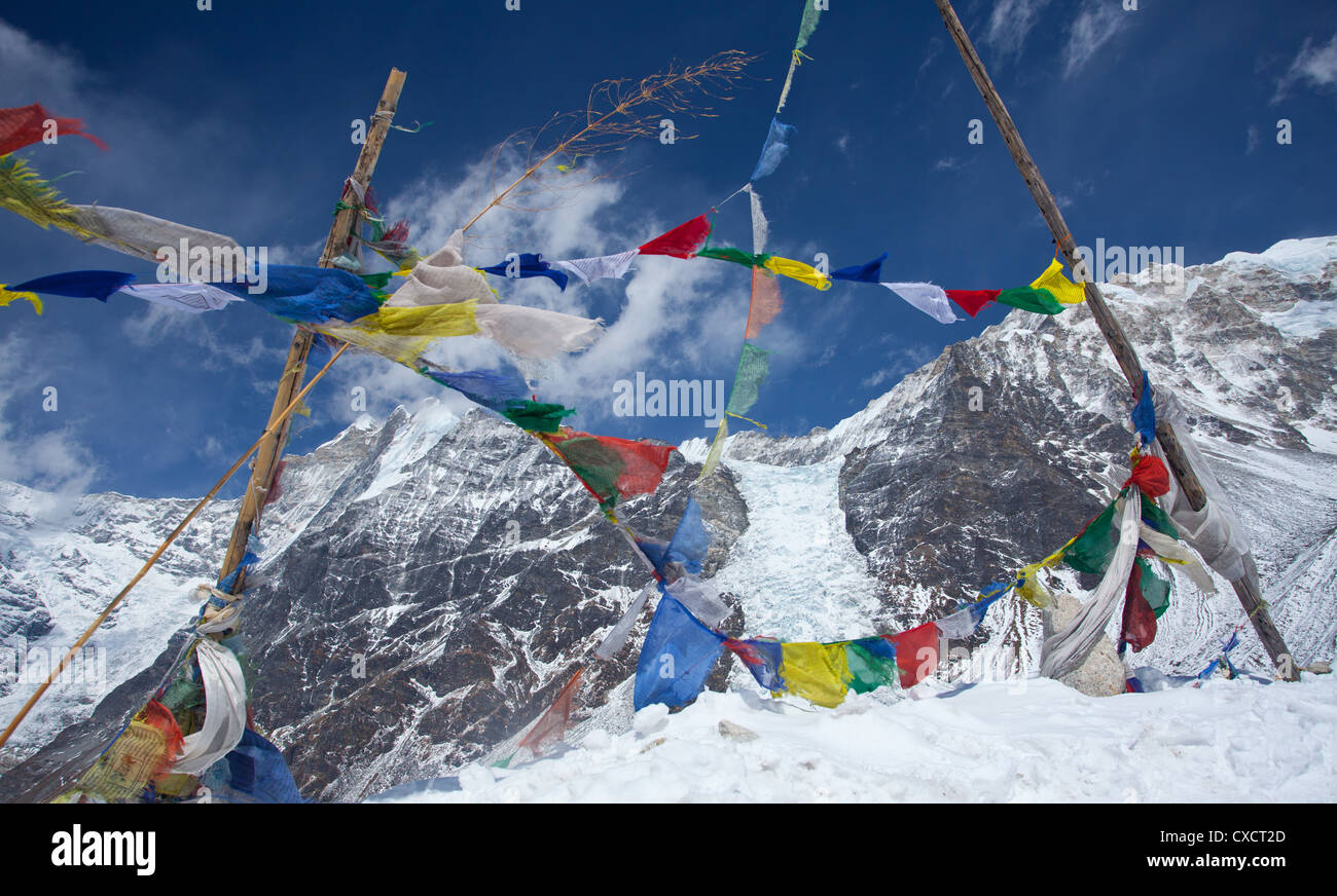 Prayerflags at the top of a mountain with a view of Kyimoshung Ri glacier in the background, Langtang Valley, Nepal - Stock Image