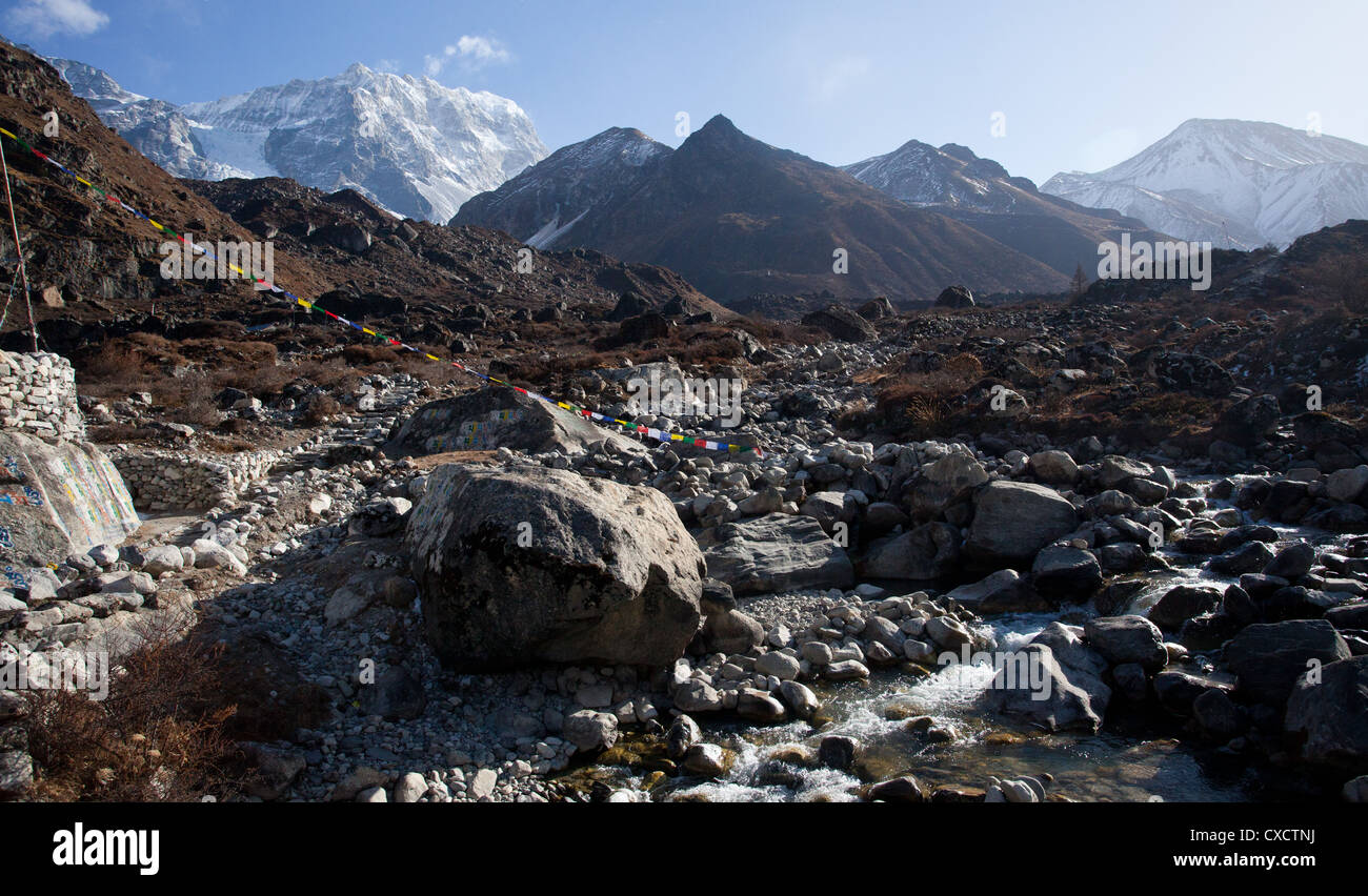 Colourful prayerflags next to a rocky river in the Langtang valley, surrounded by snowcapped mountains, Nepal - Stock Image