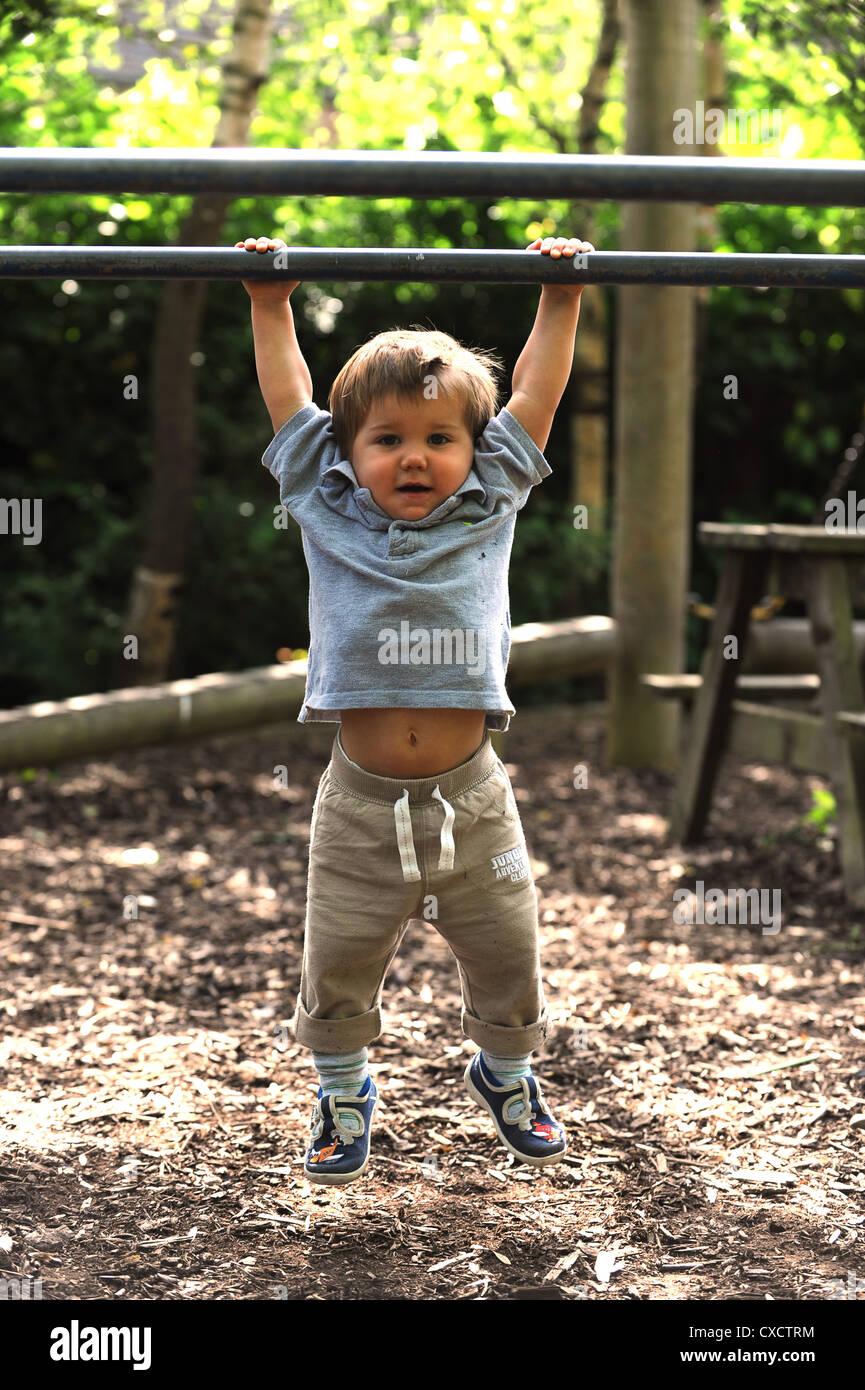 Tough looking toddler hanging to bar - Stock Image