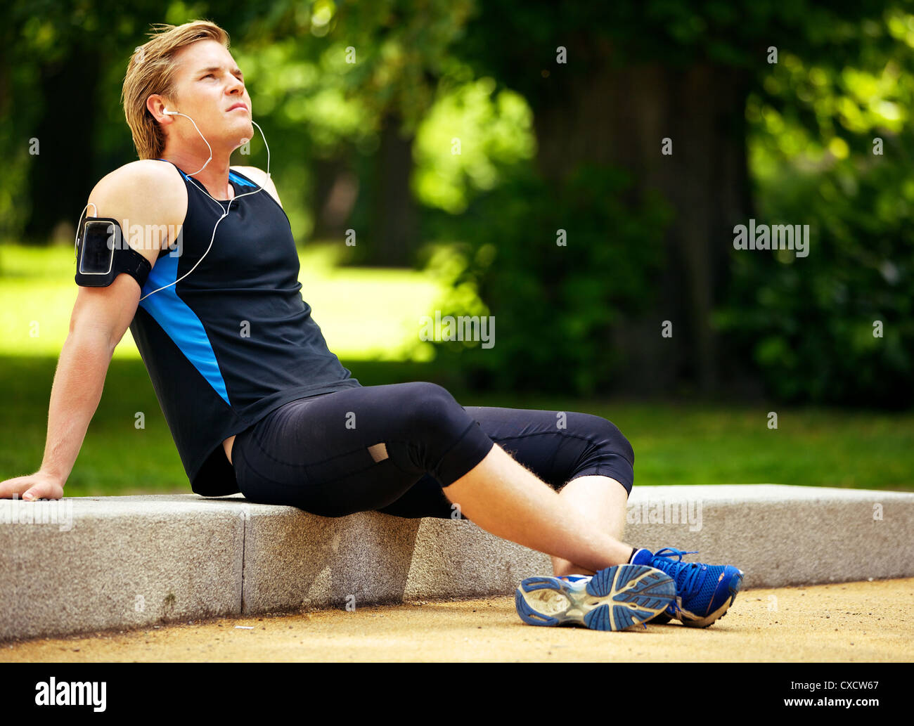 Young athlete relaxing and listening to mp3 - Stock Image