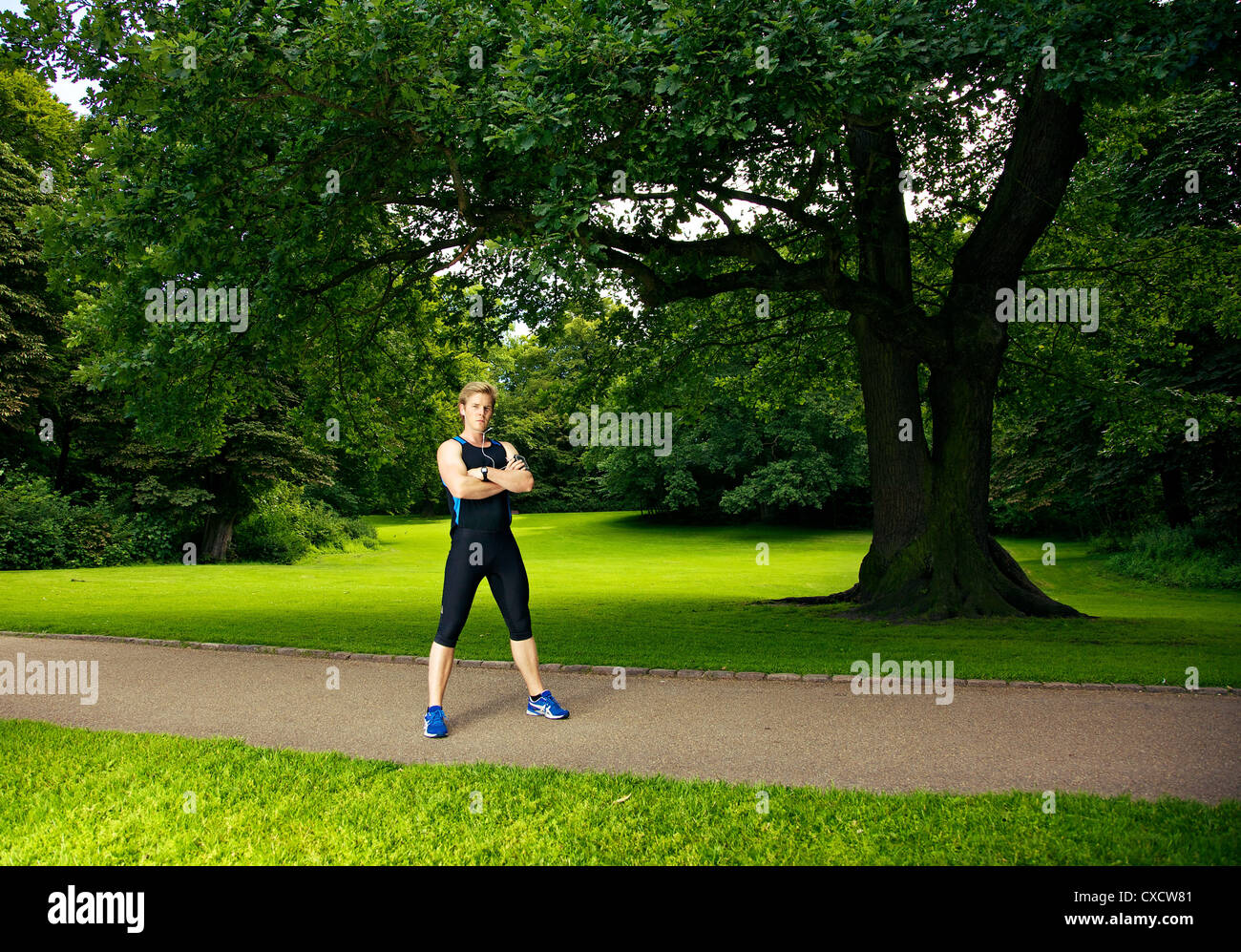 Athlete in the park posing with trees in the background - Stock Image