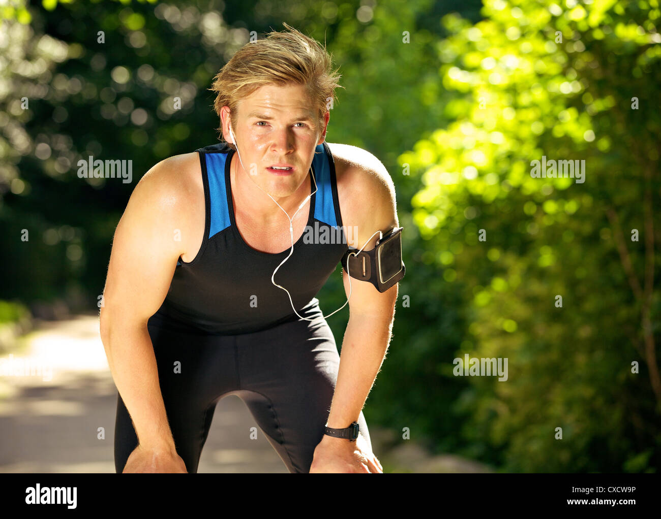 Exhausted athlete taking his break after a tiring workout - Stock Image
