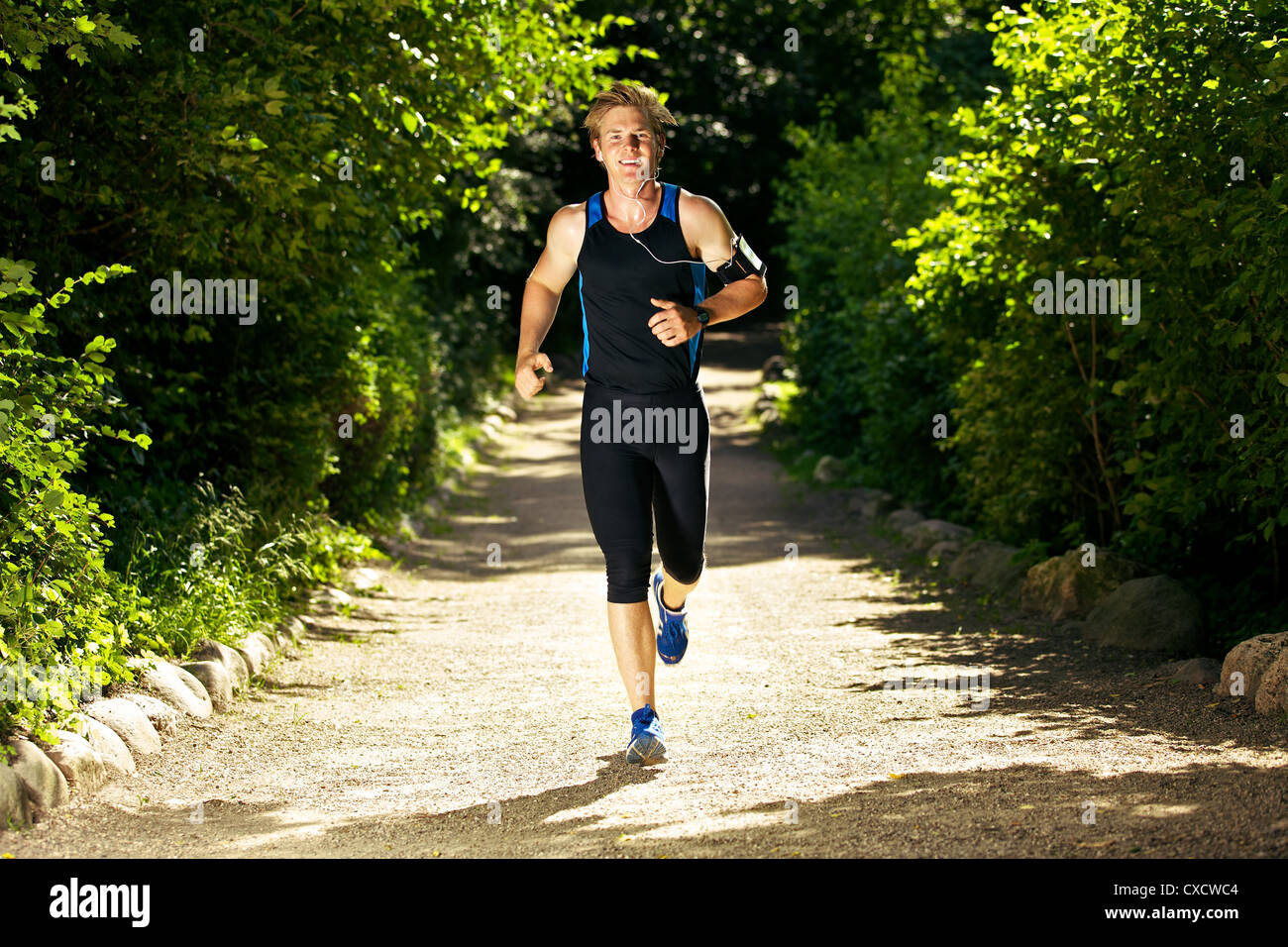 Sweaty man jogging while listening to music - Stock Image