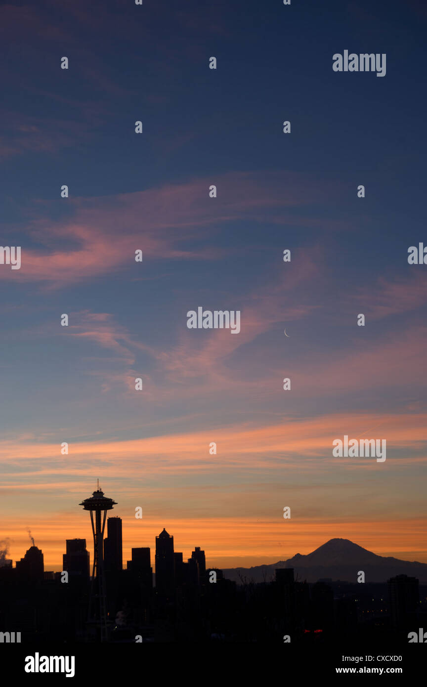 Silhouette of Seattle skyline with moon and Mount Rainier in distance, taken from Kerry Park, Seattle, Washington - Stock Image
