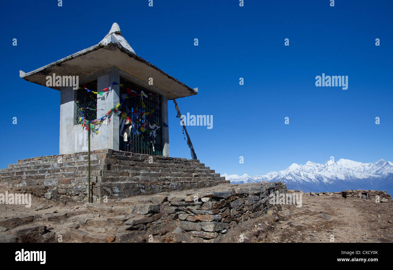 Buddhist shrine and prayer flags, with snow-capped mountains in the distance, Nepal - Stock Image
