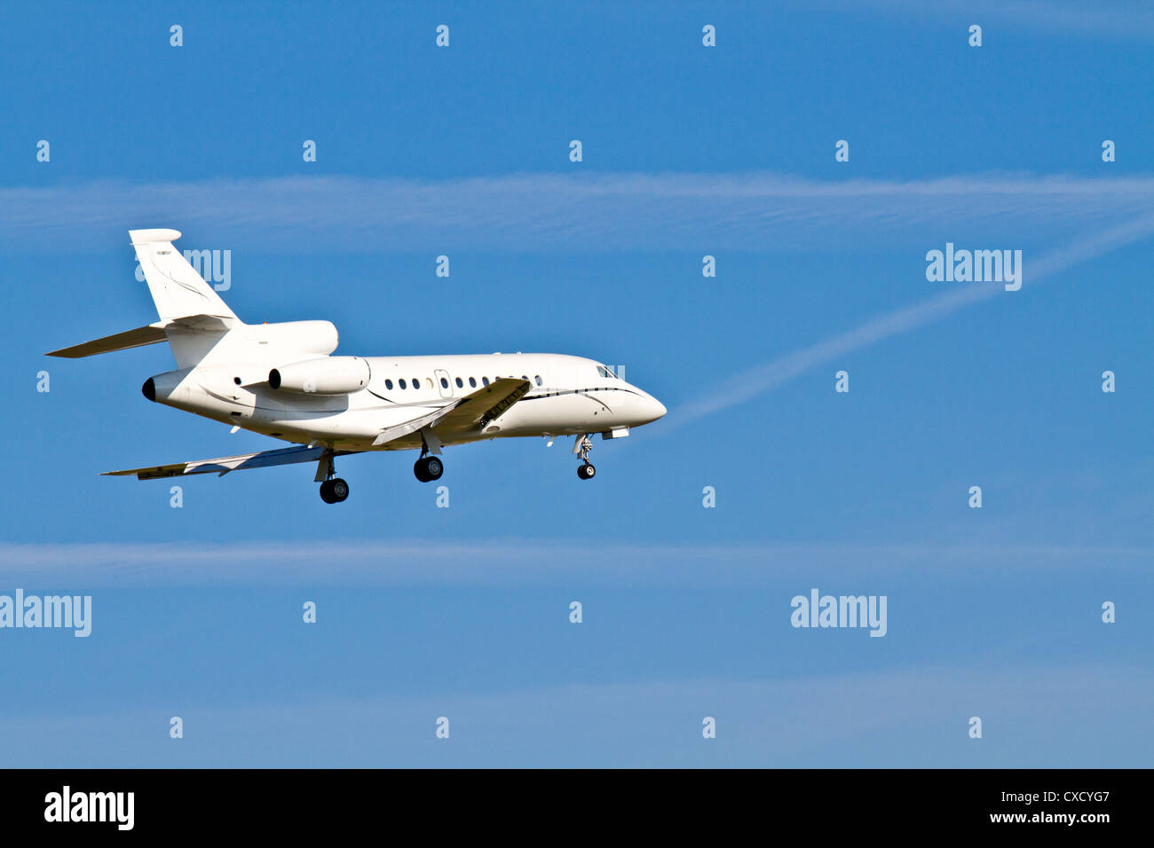 Landing Aircraft / Private Jet (blue sky) - Stock Image