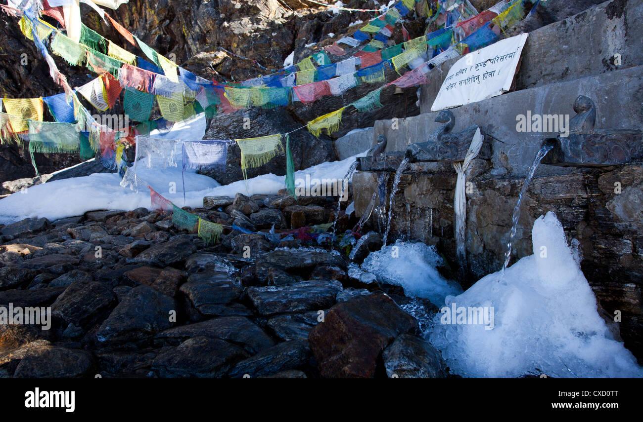Buddhist prayer flags next to drinking water fountains at Gosaikunda, Nepal - Stock Image